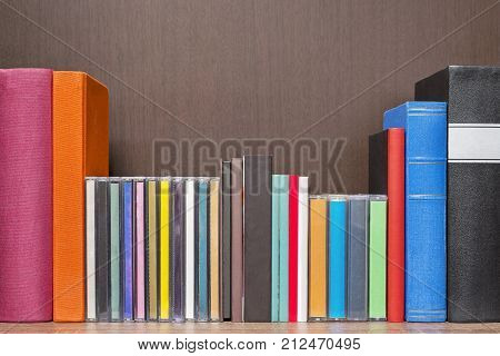 stack of new colorful books, cd and cassettes in the book self