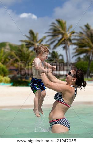 Young happy mother playing with her little son in the ocean