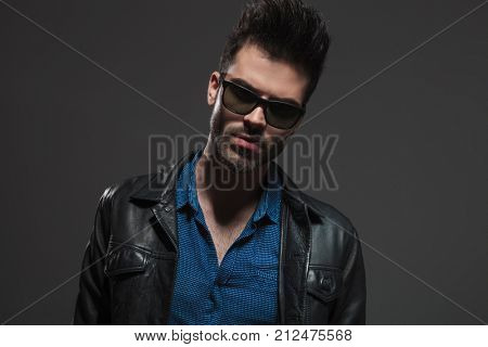 hot man in leather jacket and sunglasses poses for the camera on grey background