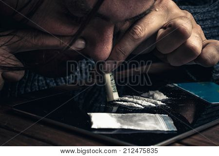 Man taking or sniffing drugs, snorting cocaine, Drug abuse concept