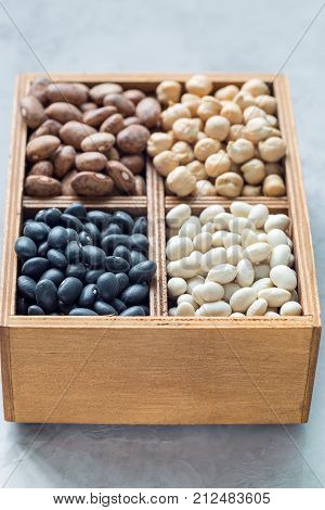 Different kinds of beans: black pinto white and chickpeas in a wooden box on a gray concrete background vertical