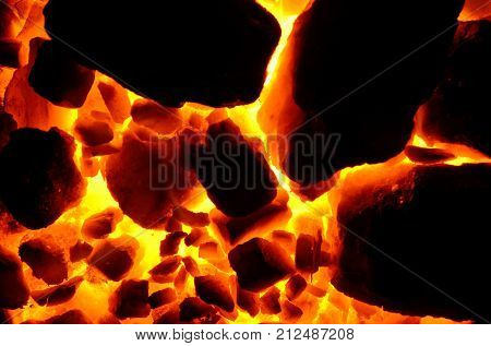 Background of burning and flaring pieces of coal anthracite of different fractions.