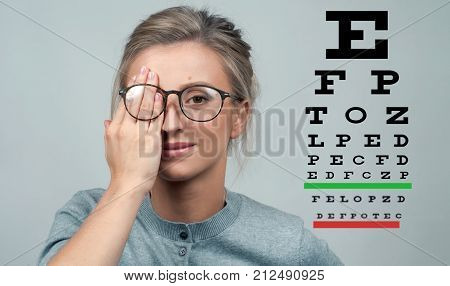 Woman On The Background Of Eye Test Chart, Eye Care Concept