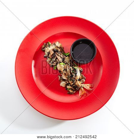 Teppanyaki Japanese and Korean Grill Food - Shrimp with vegetables sprinkled with fresh herbs and sesame seeds with sauce in black bowl in red plate. Top View
