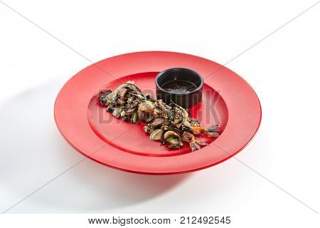 Teppanyaki Japanese and Korean Grill Food - Shrimp with vegetables sprinkled with fresh herbs and sesame seeds with sauce in black bowl in red plate