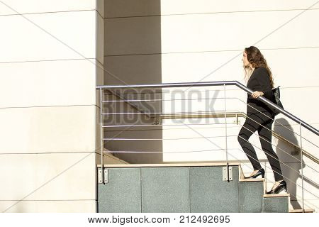 Confident young business intern moving up ladder symbolizing brilliant start in career. Purposeful businesswoman seeking success. Promotion concept
