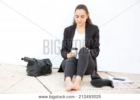 Pensive attractive girl resting outdoors and sitting on asphalt leaning on wall. Sad young intern in formalwear upset about first work day. Modern lady drinking coffee. Freelancer concept