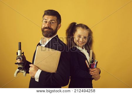 Home schooling and back to school concept. Kid and dad hold microscope book and stationery. Girl and man in suit and school uniform. Father and schoolgirl with happy faces on yellow background