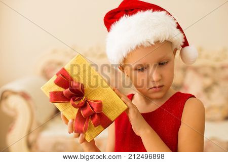 Concentrated kid thinking of New Years gift and shaking packaged box. Serious cute girl in Santa hat anticipating present. Favorite holiday of children concept