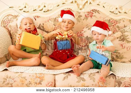 Dreamy children opening their Christmas gifts and sitting on luxurious sofa. Excited siblings in Santa hats getting long-awaited gifts. Christmas miracles concept