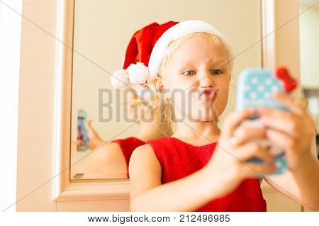 Funny grimacing girl making selfie with smartphone. Emotional kid in Santa hat photographing herself to make post in social media. Child and gadget concept
