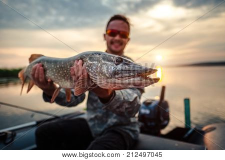 Happy angler holds pike fish (Esox lucius)  sitting in a boat with river on the background