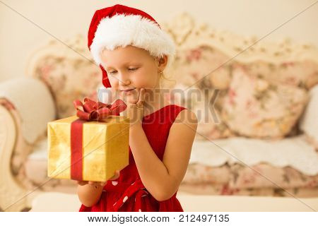 Pensive girl guessing what is in gift box. Smiling pretty kid holding Christmas present and thinking of surprise. Anticipation concept