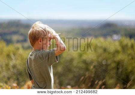 A little 8 year old boy out on a nature hike is sheilding his eyes from the sun as he looks out over the trees while high up on a bluff.