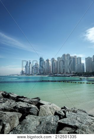 A sea front residential and commercial buildings at Dubai Marina, UAE. A view from a beach.