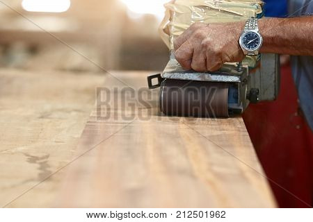 Front view of belt sander working on a piece wood with hands of worker with copy space. Selective focus and shallow depth of field.