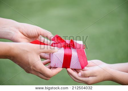 Mother hand giving a gift box to her child. Holidays present christmas and happiness concept.
