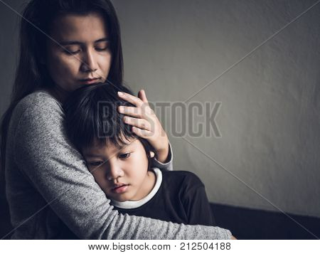 Sad little boy being hugged by his mother at home. Parenthood Love and togetherness concept.