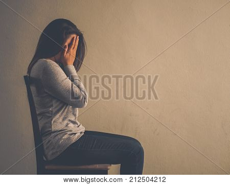 Depressed woman sitting on a chair in dark room at home. Lonly sad emotion concept.