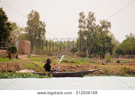 BAMAKO, MALI - CIRCA FEBRUARY 2012: Bozo woman scooping water out of a pirogue on the river Niger just outside Bamako.