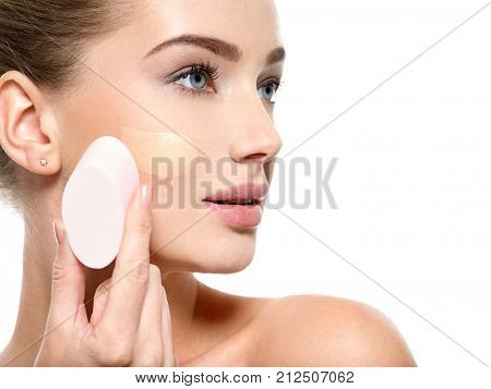 Girl applies  tonal foundation  on the face use sponge. Woman makes makeup.