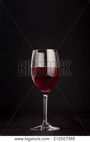 Wine glass with red wine on elegant dark black wooden background copy space vertical. Template for portfolio advertising design branding identity cover magazine bar and restaurant menu.