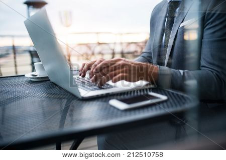 Unrecognizable mature businessman with laptop and smartphone sitting outside a cafe. Man working on a laptop. Shot through glass.
