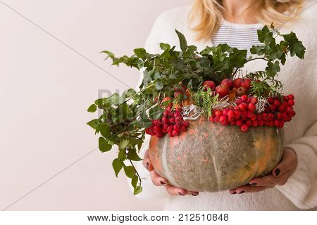 Closeup of beautiful autumn composition in a pumpkin vase in woman's hands. Flower and red berries arrangement in a pumpkin vase for Halloween. Table setting.