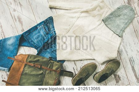 Flat-lay of Fall lady' s clothes outfit. Ecru colored knitted woolen sweater with braids, blue denim jeans, haki suede oxford leather boots, large backpack, cap over parquet background, top view