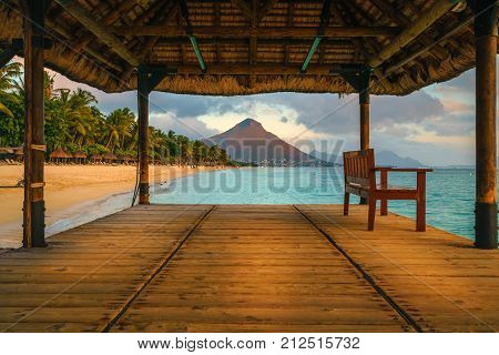 Wonderful view across the pier on the left the tropical beach and in the background a beautiful mountain illuminated by red during sunset Mauritius