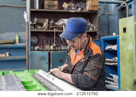 LIPETSK, RUSSIA - JUNE 15, 2017: Lipetsk Machine Tool Plant. Work on the preparation of the bed of a metal-cutting machine for assembly. The locksmith performs a manual scraping operation.