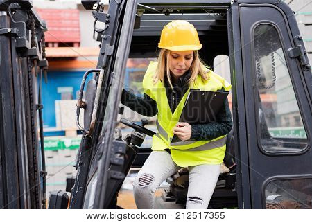 Female forklift truck driver outside a warehouse. A woman getting out of the fork lift truck, holding notes.