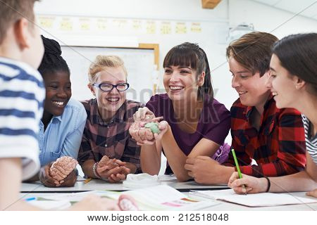 Teenage Students With Teacher In Biology Class