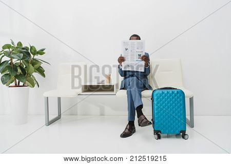 African american Businessman sitting in waiting room and reading newspaper
