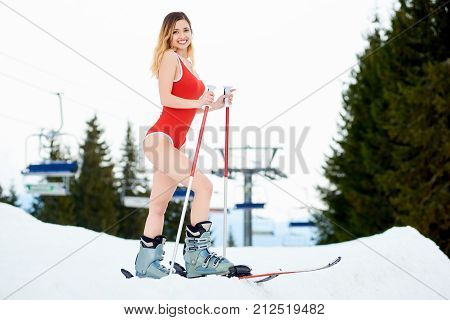 Young Sexy Woman Skier Wearing Red Swimsuit, Boots And Skis, Holding Poles, Standing On The Top Of T