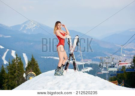 Smiling Young Woman Skier Wearing Red Swimsuit, Standing With Skis On The Top Of The Hill At Ski Res