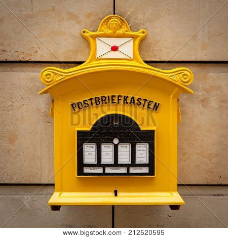 An old vintage yellow mailbox in Dresden Germany with inscription