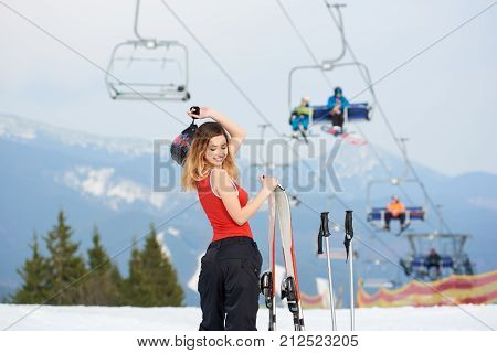 Beautiful Woman Skier Wearing Ski Pants And Red Swimsuit, Standing With Ski Equipment At Winter Ski