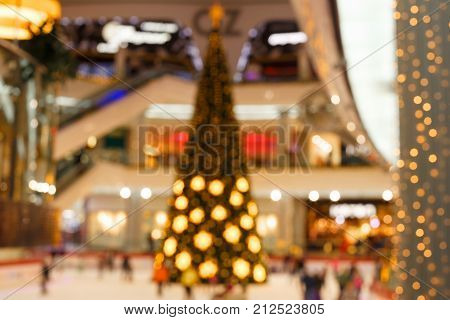 Giant Christmas tree in shopping mall. Blurred background. Christmas tree with gold decoration in shopping mall.Christmas clearance sales at the shopping mall. Elegant tree in a shopping mall