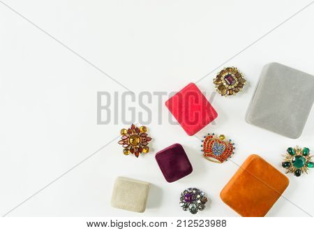 Woman's Jewelry. Vintage jewelry background. Beautiful bright rhinestone brooches and jewelry boxes on white background. Flat lay top view with copy space