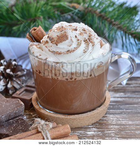 Cup of hot chocolate cocoa with whipped cream and chocolate crumbs on wooden table with  christmas  decoration. Delicious cold weather beverage concept.