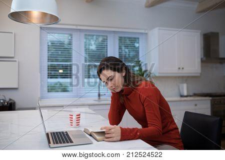 Beautiful woman reading novel at table