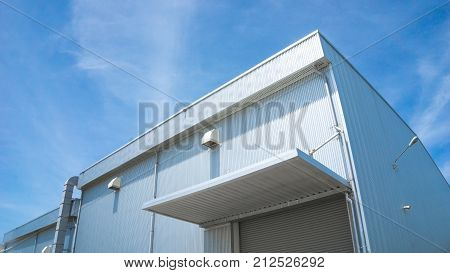 actory warehouse and industrial concept - Wall and roof of Factory or warehouse building in industrial estate with blue sky and copyspace