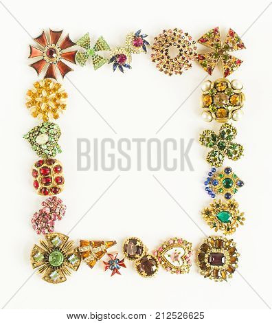 Woman's Jewellery. Frame with old vintage brooches. Beautiful bright rhinestones brooches on white. Not isolated. Flat lay top view.