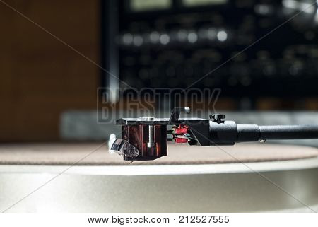Moving magnet cartridge on the tonearm on a blurred background