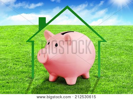 Savings for a house concept piggy bank on green field