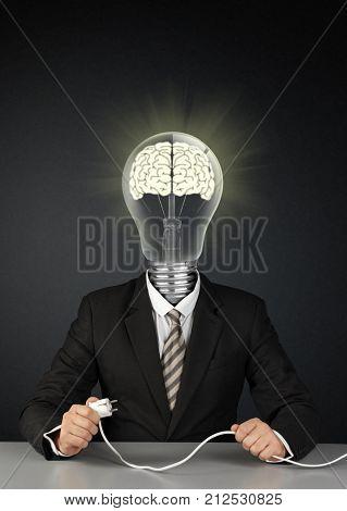 Businessman with light bulb head and plug switch brain creative concept on black