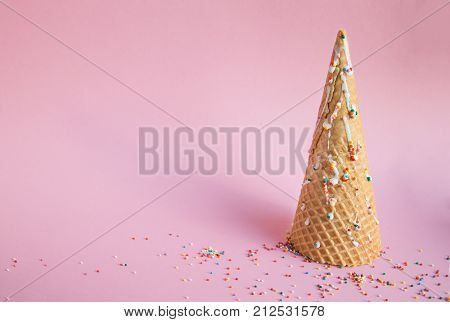 Waffle cone of ice cream as looks like Christmas tree decorated with sweet multi-colored balls on a pink background. concept christmas, new year.