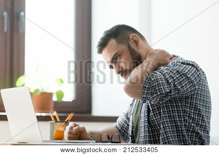 Troubled bearded man massages aching neck with a pained expression, working on laptop computer, deep in thoughts.