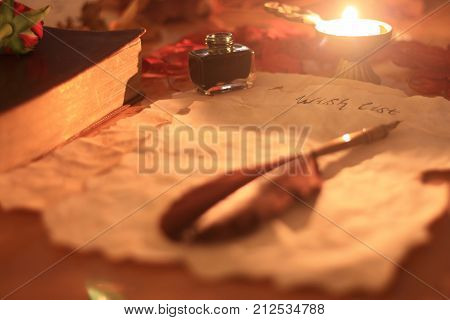 Old wishlist paper with feather pen and ink a candle rose and Bible on wooden table